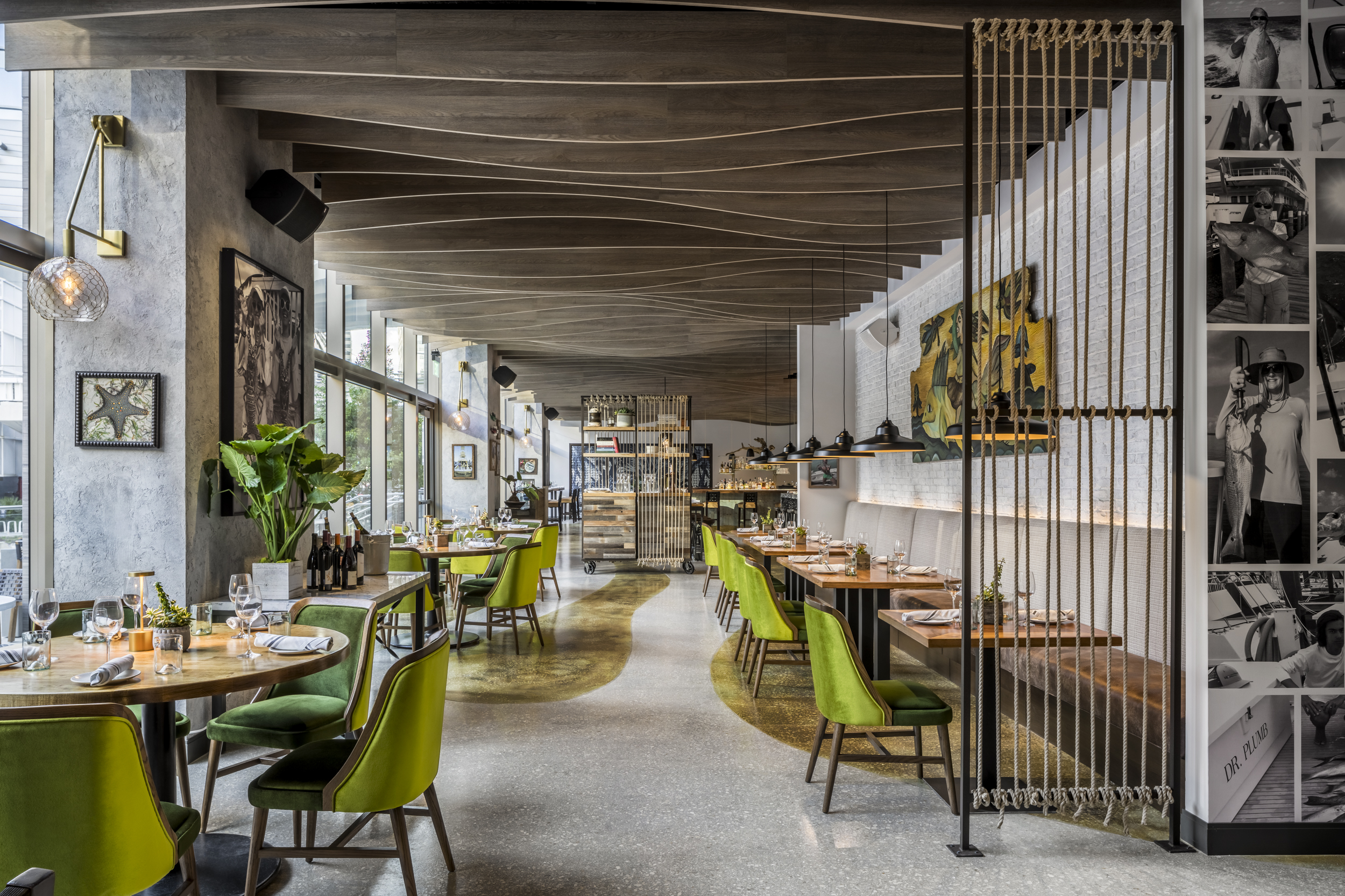 River Oyster Bar with green upholstered chairs, artwork and rope screen