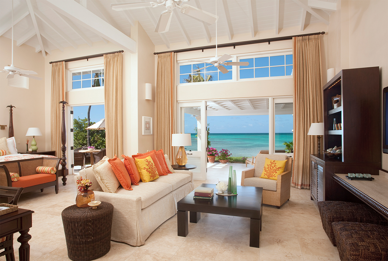 Seating area of a hotel room with an exit to the beach at Jumby Bay Resort, Antigua