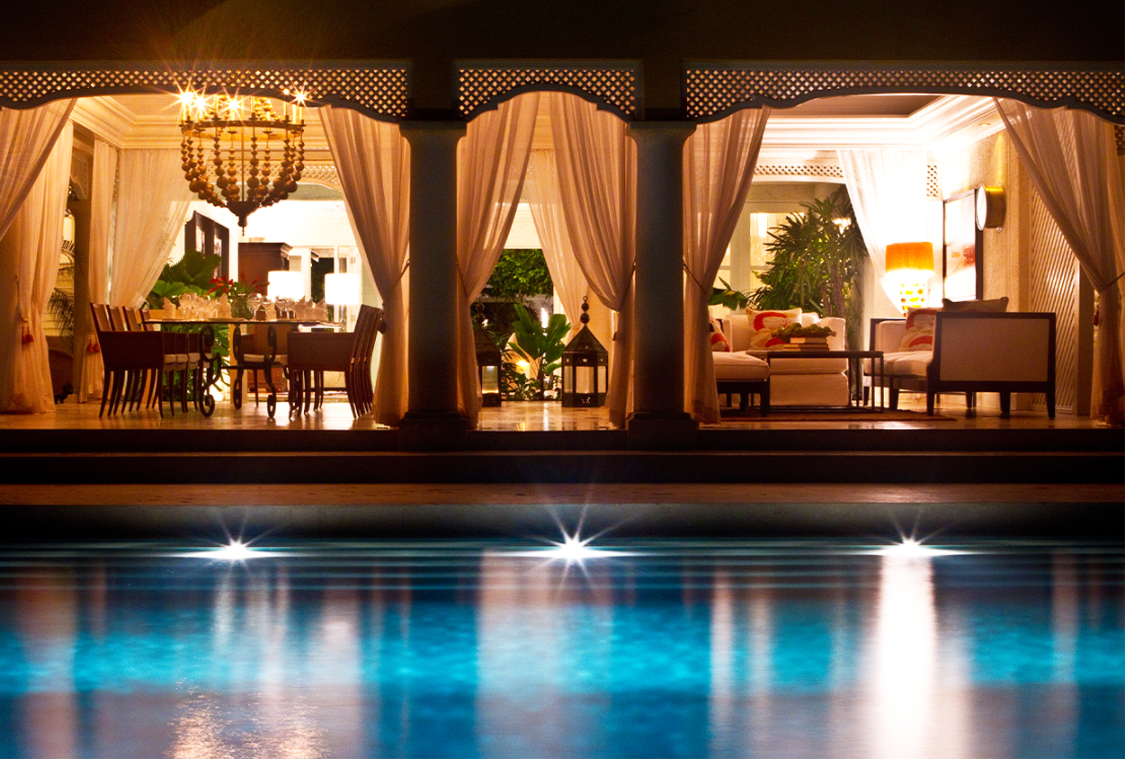 Outdoor pool, dining, and seating area at night in Roaring Pavilion, Jamaica