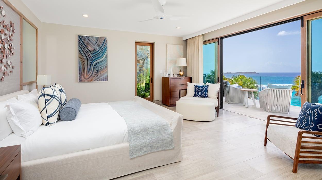 Junior Suite Bedroom overlooking the ocean with custom artwork and ceramics
