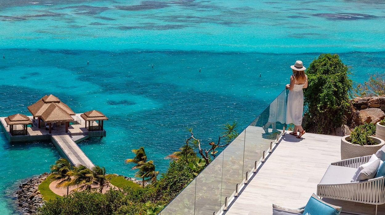 Woman on terrace overlooking ocean and gazebo in Caribbean