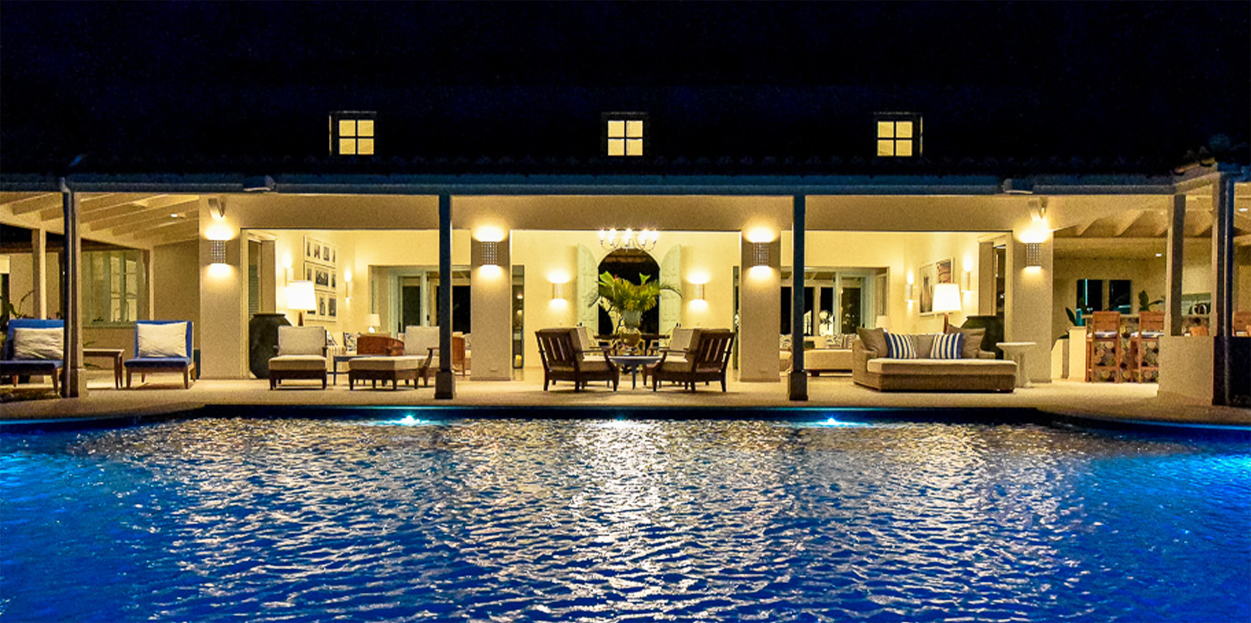 Pool and outdoor seating area at night in Private Estate Home in Jumby Bay