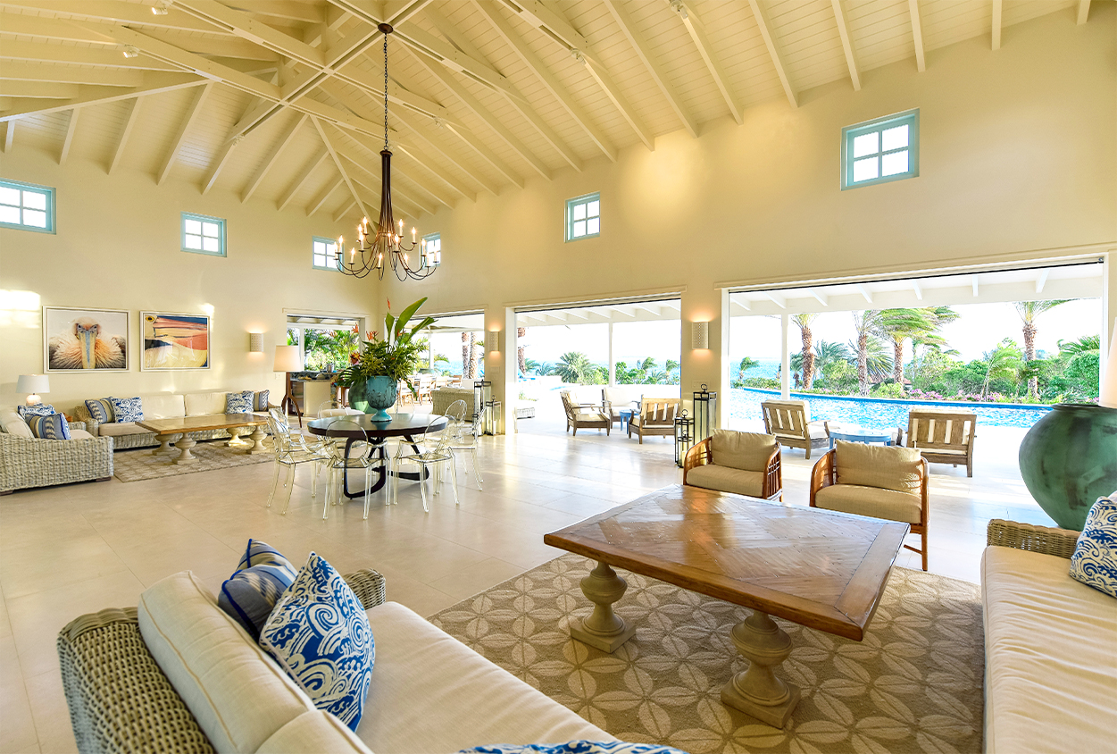 Indoor seating area with a view of the pools in Private Estate Home in Jumby Bay