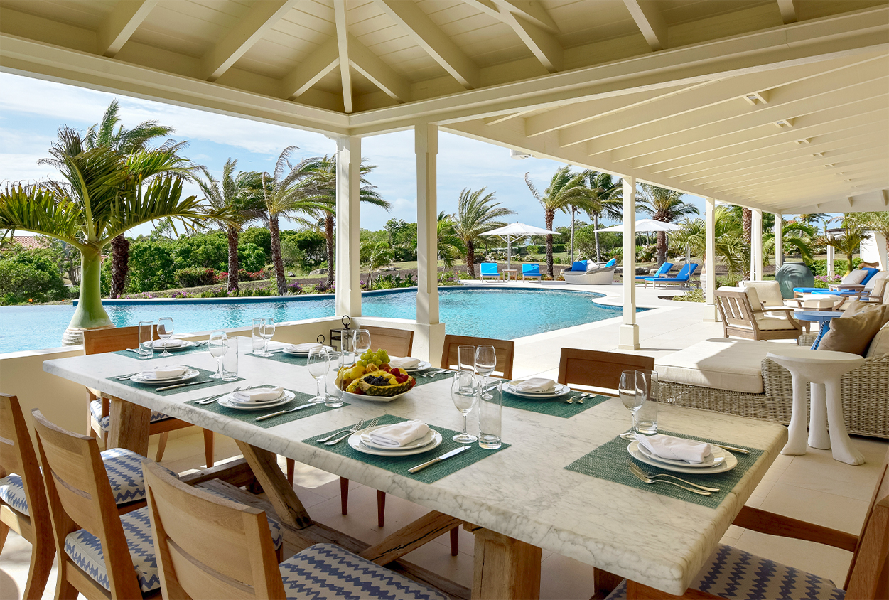 Outdoor dining area by the pool in Private Estate Home in Jumby Bay